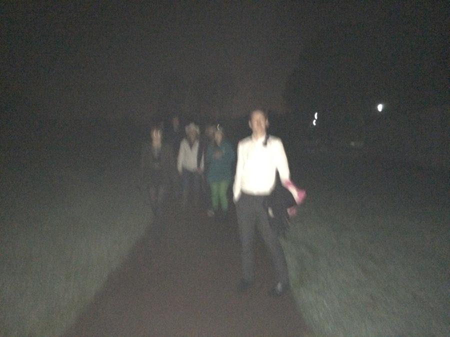 Photo of people walking in the dark.